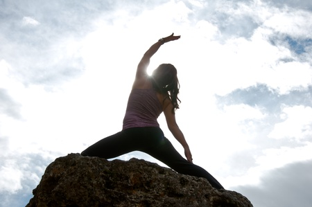 Silhouette of young attractive girl doing yoga on top of a rock with the sky and cloudy in the background Banco de Imagens - 13094342
