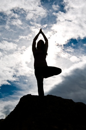 Silhouette of a young attractive girl doing yoga outside on top of a rock with sky   clouds behind her  photo