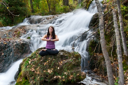 Young attractive girl sitting on a rock and meditating in a forest with a stream cascading down behind her  The water is slowed and blurred to give a dreamy looking effect  Banco de Imagens
