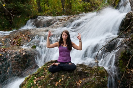 Young attractive girl sitting on a rock and meditating in a forest with a stream cascading down behind her  The water is slowed and blurred to give a dreamy looking effect  photo