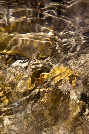 Close up of clean and clear water from a stream with ripples and sun reflections Banco de Imagens