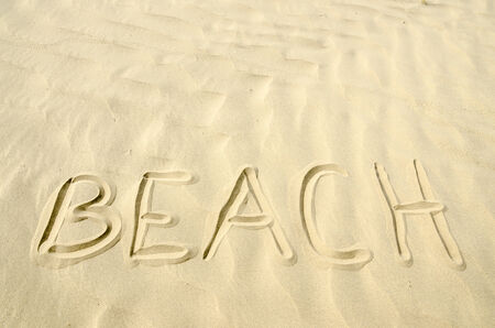 Beach written in golden sand waves photo
