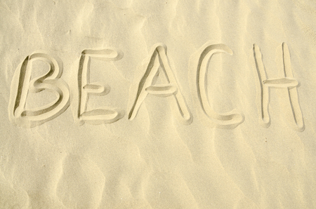 Beach written in golden sand waves photo