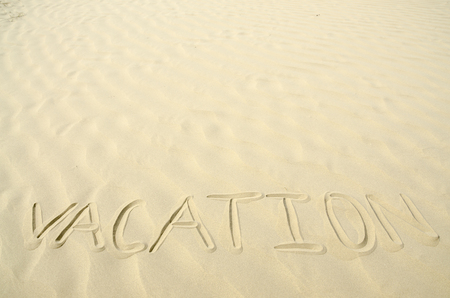 Vacation written in golden sand waves photo