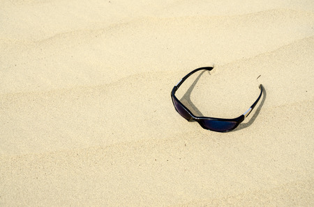 Sunglasses in the golden sand photo