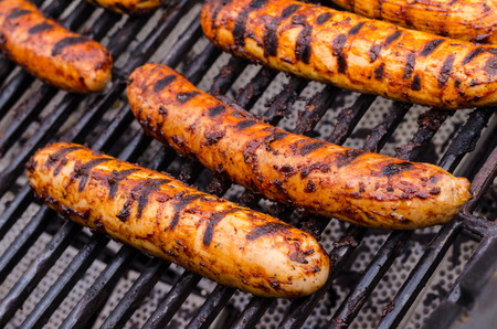 Sausage covered in sauce on grill Banco de Imagens - 31025777