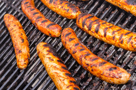 Sausage covered in sauce on grill Banco de Imagens - 31025778