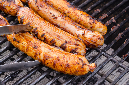Sausage covered in sauce on grill Banco de Imagens - 31025779