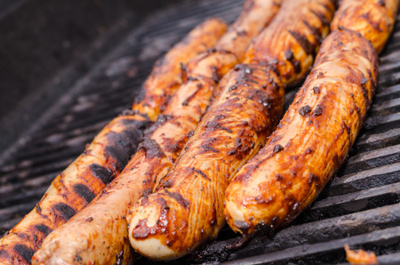Sausage covered in sauce on grill Banco de Imagens - 31025780