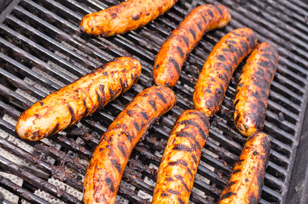 Sausage covered in sauce on grill Banco de Imagens - 31025785