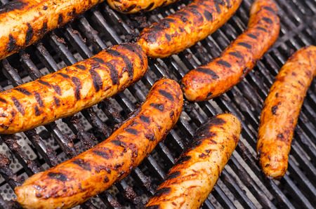 Sausage covered in sauce on grill Banco de Imagens - 31025894