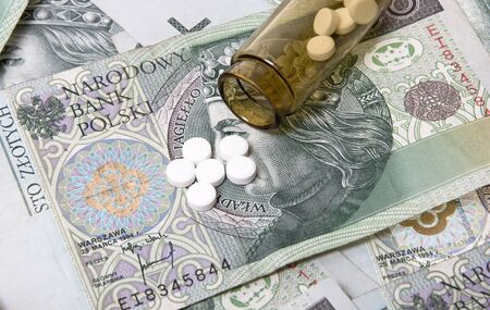 healthcare costs: Drugs on a money background,  representing rising healthcare costs. Stock Photo