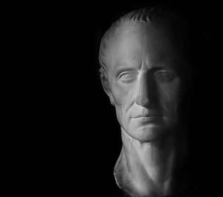 statuary: Gypsum head of Caesar on black background.