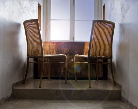 two rattan chair in front of window on sunrise photo
