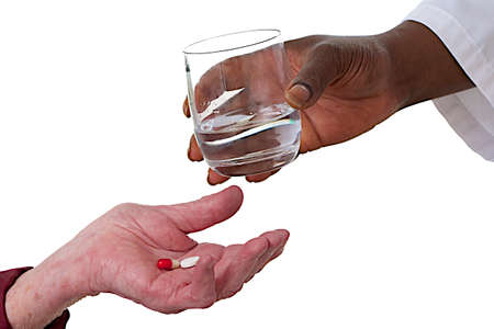hand of an old  patient holding medicine,hand of the nurse giving glass of water photo