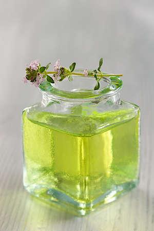 herbolaria: botella de aceite esencial con la rama de tomillo en la parte superior