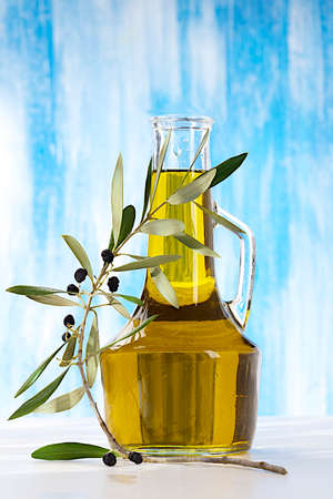 carafe: Olives, oil and a blossoming branch of an olive tree. Isolated on a blue background