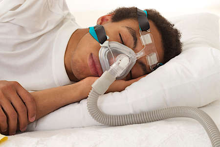masks: young mulatto man  sleeping with apnea and CPAP machine  Stock Photo