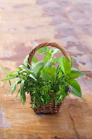 Little basket of  aromatic herbs  on old wooden plank background photo