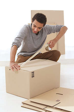 young mulatto man closing a moving box  with tape