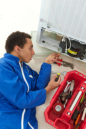 troubleshooting: Repairman makes refrigerator appliance troubleshooting and maintenance works  Stock Photo