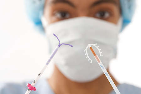 Young doctor showing two type of  IUD birth control copper coil device in hand, used for contraception