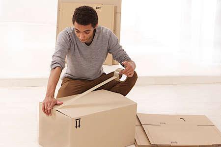 mulatto: young mulatto man closing a moving box  with tape