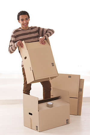 Young mulatto man packing boxes  photo