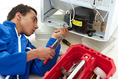Repairman makes refrigerator appliance troubleshooting and maintenance works  Stock Photo