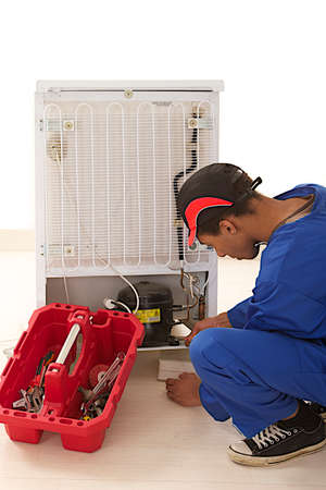 Repairman makes refrigerator appliance troubleshooting and maintenance works  photo