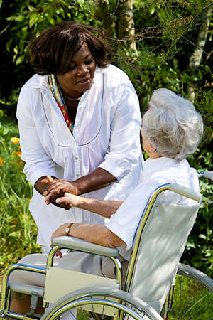 disabled seniors: Afro-american caregiver talking to disabled senior woman outdoors