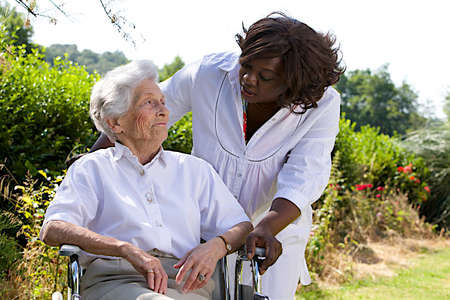 giver: Afro-american caregiver talking to disabled senior woman outdoors