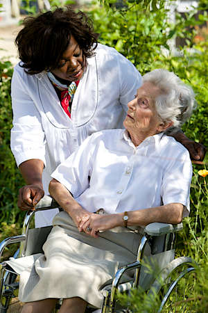 giver: friendly care giver talking to disabled senior patient outdoor