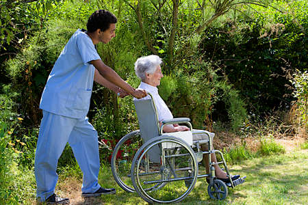 Young hospital staff pushing  happy senior patient in wheelchair outdoors  Stock Photo