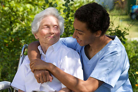 Senior woman with her very embracing and caring  caregiver outdoor photo