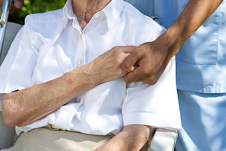 comforting: Symbol of comfort and support from care giver to elderly woman outdoor holding her hand