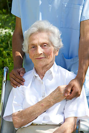 Symbol of comfort and support from care giver to smiling elderly woman outdoor photo