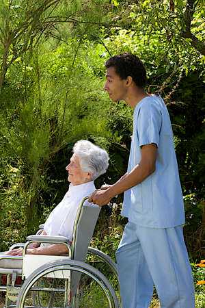Young hospital staff pushing  happy senior patient in wheelchair outdoors  photo