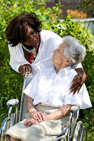 giver: S�mbolo de la comodidad y el apoyo del cuidador habla con la mujer al aire libre ancianos Foto de archivo