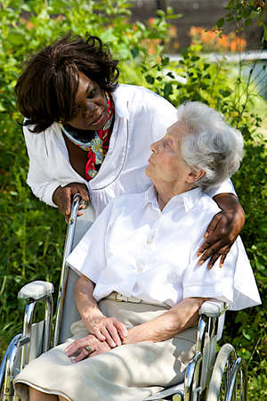 care giver: Symbol of comfort and support from care giver talking to elderly woman outdoor Stock Photo