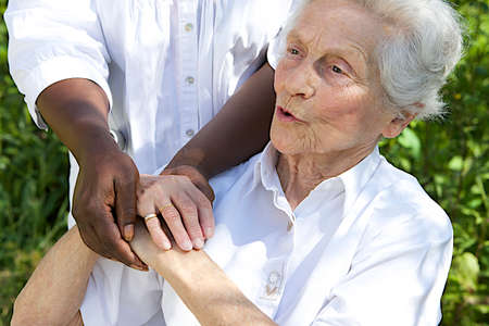 Symbol of comfort and support from care giver to smiling elderly woman outdoor