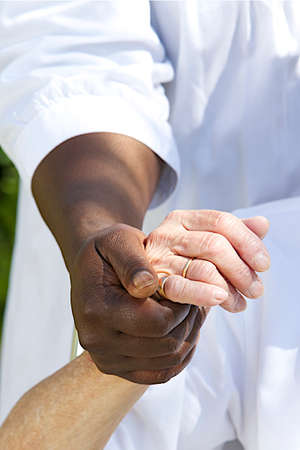 Image Symbol of comfort and support from care giver to elderly woman outdoor holding her hand Stock Photo
