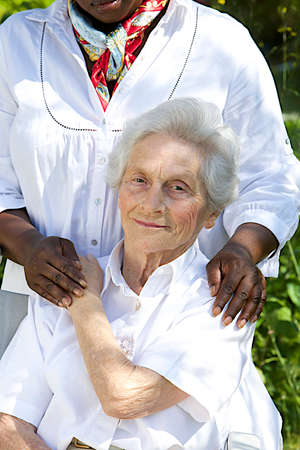 care giver: Image of comfort and support from care giver to smiling elderly woman outdoor Stock Photo
