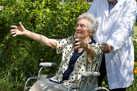 Happy elderly  woman in wheelchair with open arms, welcoming photo