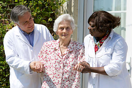 the elderly residence: caregivers assisting  senior patient  walking outdoors