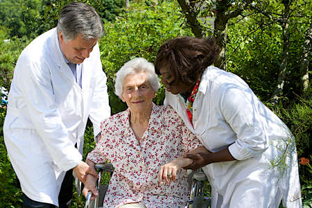 the elderly residence: caregivers assisting  senior patient  in wheelchair outdoor