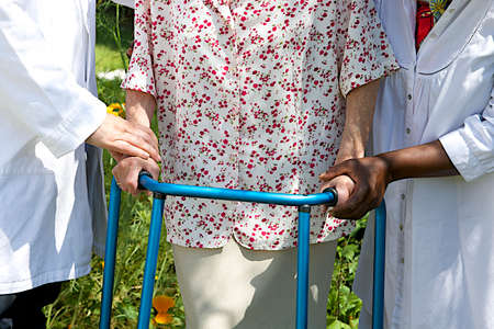 care giver helping senior patient with walker  outdoor photo