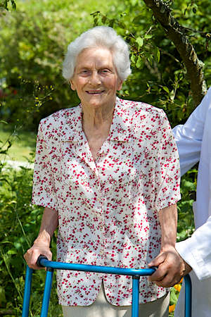 care giver: care giver helping senior patient with walker  outdoor