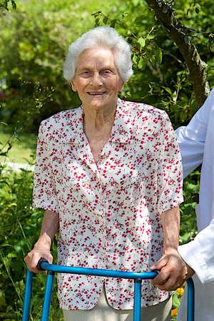 giver: Cuidador ayudar al paciente mayor con andador al aire libre