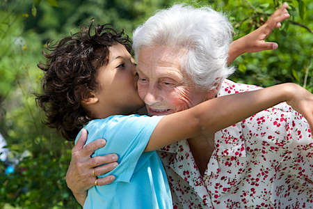 grand son: Portrait of grand son hugging and embracing  happy grandmother in the  garden  Stock Photo